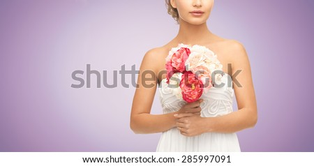 wedding, holidays, people and celebration concept- bride or woman with bouquet of flowers over violet background