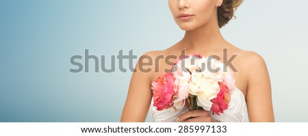 wedding, holidays, people and celebration concept- bride or woman with bouquet of flowers over blue background