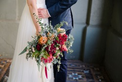 Wedding image of bride and groom with colourful wedding bouquet of native australian flowers, eucalyptus, wattle and proteas.