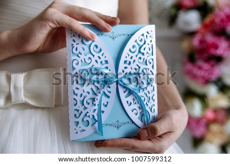 Wedding invitation blue card in the hands of the bride #1007599312