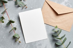 Wedding invitation card mockup with envelope and eucalyptus branches on grey concrete background, top view