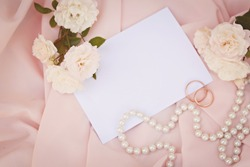 Wedding invitation card on pink silk background