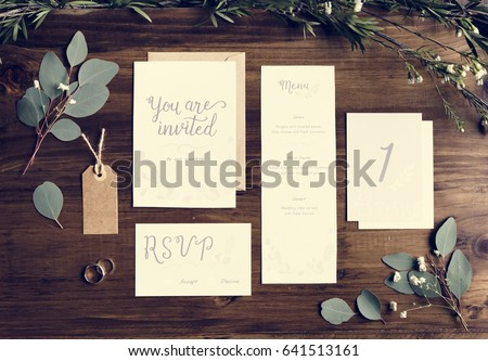 Wedding Invitation Cards Papers Laying on Table Decorate With Leaves #641513161