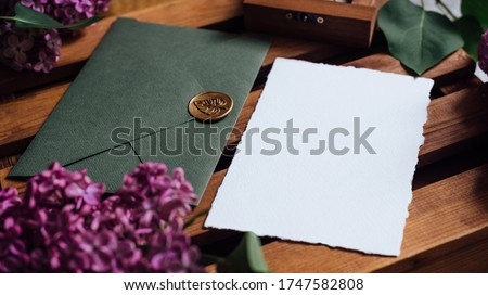 Wedding invitation set with card mockups. Wedding invitation set with a dark green envelope, purple lilac flowers on a wooden background. Flat lay workspace. Wedding Flat lay Foto d'archivio ©