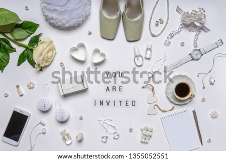 Wedding invitation. Text YOU ARE INVITED, empty calendar date for your event and stylish feminine accessories, bridal decorative items, cosmetics, jewellery and rose flower on white background. Mockup #1355052551