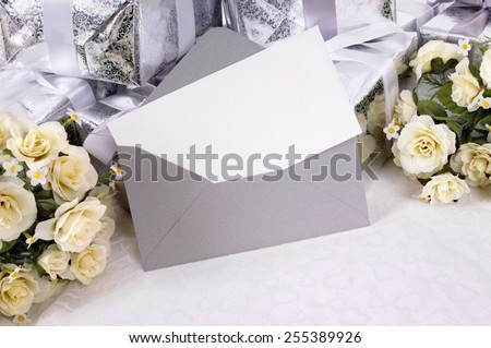 Wedding invitation - white writing paper or invitation with envelope with wedding gifts and white rose bouquets.  Wedding card or thank you note.  Space for copy.