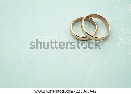 Wedding invitation with rose gold rings on wood background