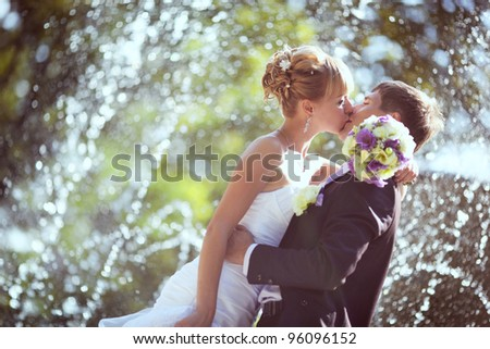 wedding kiss in the park with a fountain