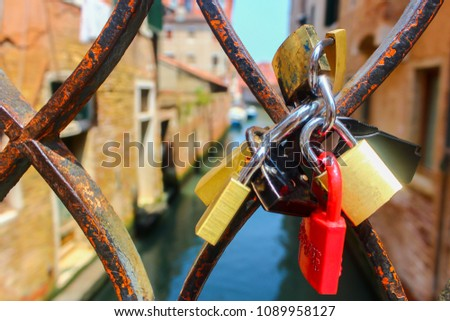 Wedding locks of lovers on old rusty bridge handrail grid fence in Venice on water background #1089958127
