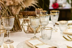 wedding luxury table setting crystal wine glass and gold forks and knives. Catering banquet. table decor for celebration anniversary, christmas, new year. table settin grestaurant. selective focus
