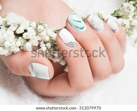 Wedding manicure for the bride in gentle tones with flowers. Nail Design. Close-up.