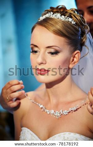 Wedding necklaces Brides in hands of groom