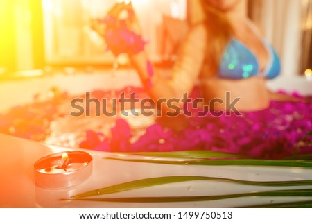 wedding night.beautiful bride and handsome groom relaxing in bath tropical flowers at luxury hotel resort.man and woman kissing and hugging romantic fruits, candles and champagne.sex in the water