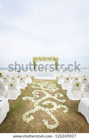 Wedding on the beach. A beautiful wedding arch, decorated with flowers, chairs for guests, floral pattern of white orchids on the green grass against the sea and sky.