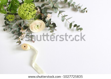 Wedding or birthday mock-up scene with floral bouquet of Persian buttercup, Ranunculus flower, eucalyptus leaves, pink cherry tree blossoms and spool of silk ribbon Feminine styled stock image. Flat l #1027725835