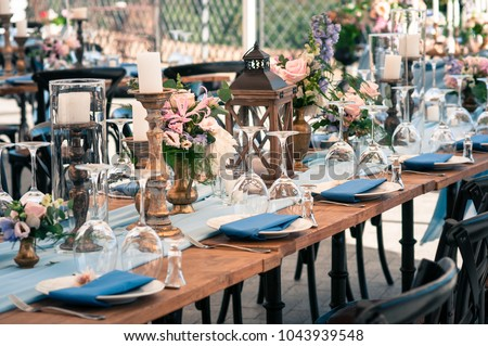 Wedding or other catered event setting, flowers, candles, white plates, blue napkins, wooden tables, Event decoration, outdoors, summer time