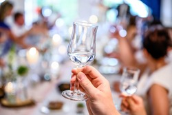Wedding or party concept. Hand with a glass of vodka guest makes a toast, raising a glass