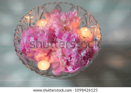 Wedding or SPA decorations, peonies and Floating candles in water in a crystal vase