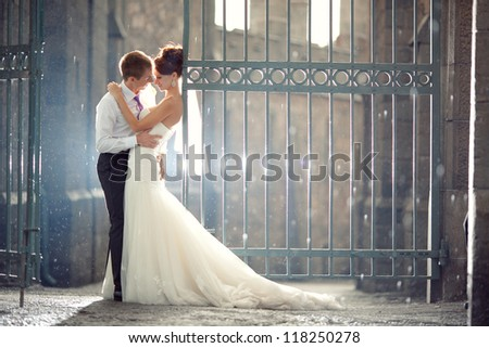 wedding pair hugging and kissing at the gate