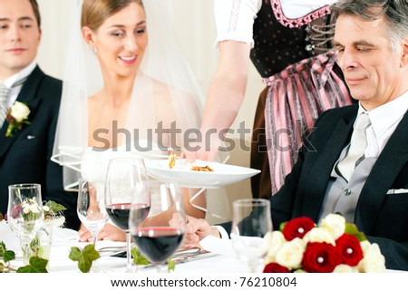 Wedding party at dinner - the dish is going to be served
