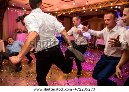 Wedding party. Groomsmen having fun and dancing at wedding banquet. Selective focus