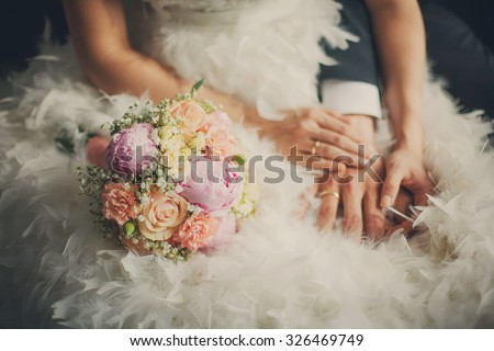Wedding pastel bouquet closeup in front of couple - groom and bride's hands with elegant manicure. Flowers lay on the dress with swan feather decor #326469749