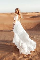 wedding photo session beautiful bride blonde in a wedding dress with a train in the hot desert dubai