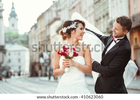 Wedding photo shooting. Bride and bridegroom walking in the city, looking at each other, holding bouquet and smiling. Groom holding veil of bride. Outdoor, cobbled street