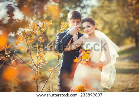 Wedding photography in autumn park where young groom kissing his hand gently bride in her wedding dress