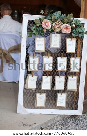 Wedding Photography: Rustic Seating Chart with Floral Decoration on a White Wooden Frame