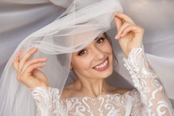Wedding portait of happy bride. Gorgeous beauty young bride portrait. Beautiful bride with wedding makeup in white wedding veil. Bridal fashion model posing in interior.