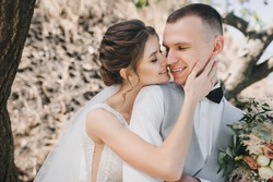 Wedding portrait of a smiling groom in a vest with a bouquet in his hands and a cute bride in a long white dress and curly hair on the background of nature near tree branches.