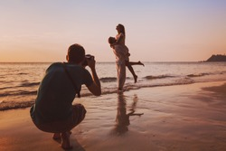 wedding portrait photographer taking photos of honeymoon couple on the beach at sunset, professional photography