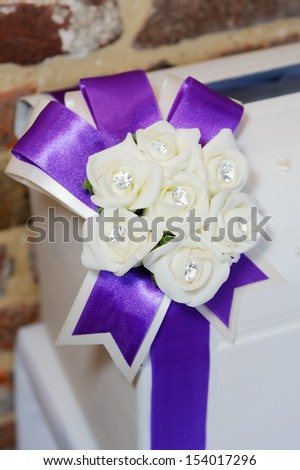 Wedding reception closeup detail of decoration is purple ribbon in a bow and white flowers