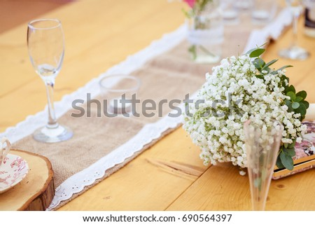 Wedding reception details. Table runner with wine glasses and gypsophila flowers as vintage style party decorations. #690564397