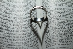 Wedding ring casting a heart onto a bible.