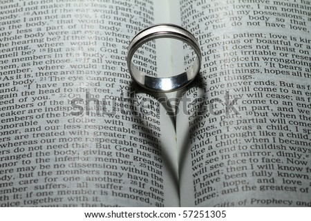 "Wedding ring casting a heart onto a bible. ""Love never ends"" verse"