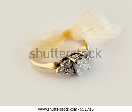Wedding ring with bow on a cream colored background.