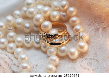 Wedding rings and a pearl necklace