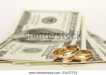 Wedding rings and money on a white background - stock photo