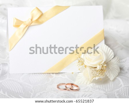 Wedding rings and wedding invitation with bow