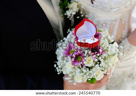 Wedding Rings Box; a red wedding rings box on a wedding bouquet with a bride and a bridegroom in bokeh background