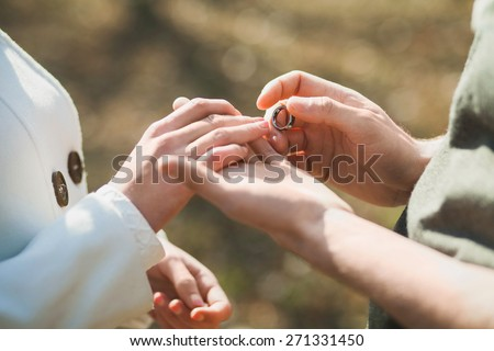 Wedding rings. Hands of bride and groom. Wedding ceremony. Wedding couple. Wedding celebration. Newlyweds. Man and woman with golden ring. Close up groom puts  wedding ring on bride