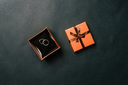 Wedding rings in a box on a dark background. Open brown box with the bride and groom's rings. Wedding concept. Top view, flat layout