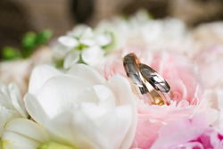 Wedding rings in delicate wedding flowers close up