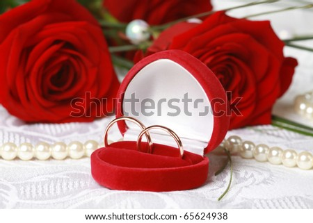 Wedding rings in red box against beautiful red roses on lace background - stock photo