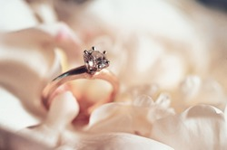 Wedding rings, jewelry and symbols attributes taken with selective focus. Holiday, celebration. Macro. Blur. Wdding bouquet on background