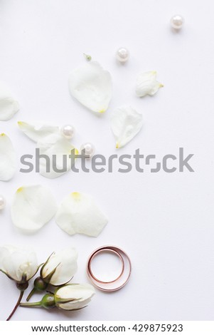 wedding rings on a background of rose petals