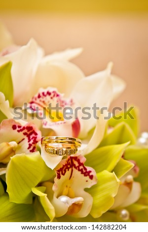 Wedding rings on a bouquet of orchids
