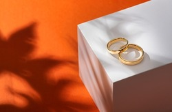 Wedding rings on a wooden box with shadows of leaves